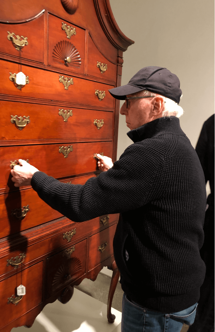 Art Auction Allan Katz opening a chest of drawers