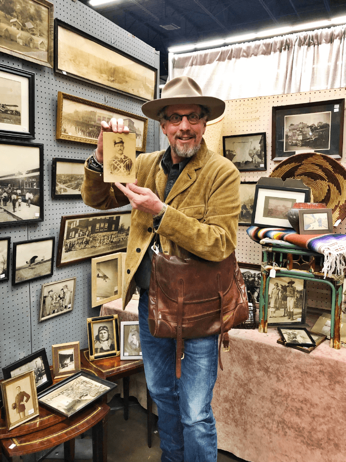 Will Evans with a photograph from the Ft. Worth Show of Art and Antiques