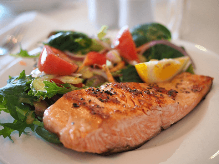 Grilled salmon with salad and a lemon wedge